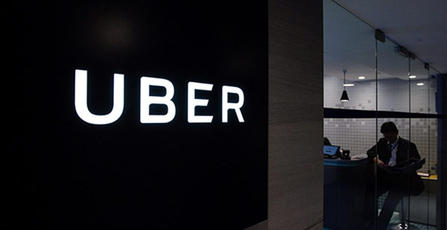 Uber signage is seen as an employee sits in the entrance of the ride hailing giants office in Hong Kong 875x450 - Uber Takes on Commuting With Express Car Pool Service